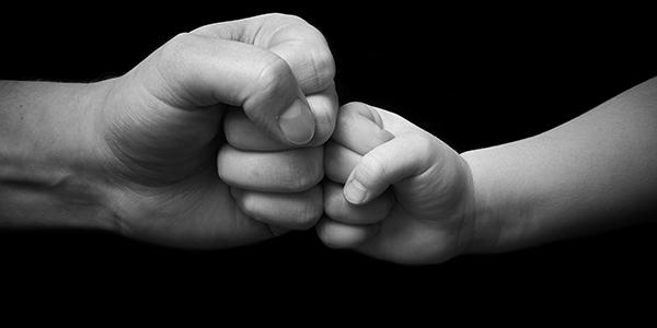 Dad fist bumping son